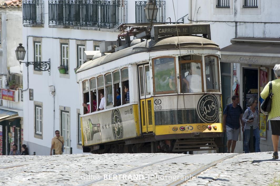LISBONNE - Un tramway electrique jaune de la ligne 28E dans les vieilles rues du quartier de l'ALFAMA