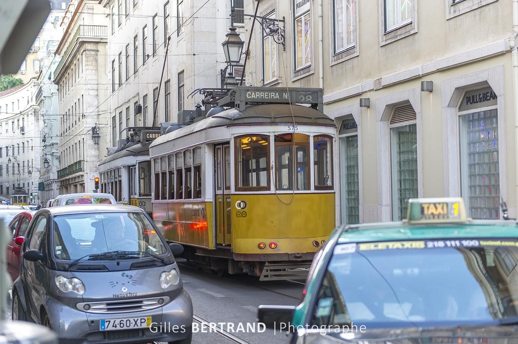 LISBONNE - Deux tramways electriques jaune de la ligne 28E au milieu de la circulation automobile