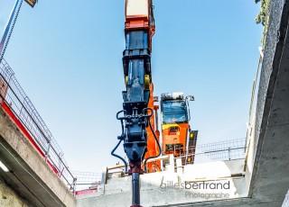 CEVA - D'une longueur totale de 16 kilometres, dont 14 sur territoire suisse, la ligne ferroviaire CEVA relie Cornavin à Annemasse, tout en desservant les principaux centres d'activites de Geneve. En connectant les reseaux CFF et SNCF qui sont aujourd'hui deux culs-de-sac ferroviaires, cette liaison permet la creation d'un veritable reseau regional (RER) transfrontalier a l'echelle de l'agglomeration franco-valdo-genevoise; Le trace de CEVA est majoritairement souterrain et necessite la construction de deux tunnels et de plusieurs tranchees couvertes; La partie superieure de cette ligne ferroviaire sera recouverte par une voix ou coulee verte pour les modes doux de deplacements. Un engin mecanique evacue la terre glaise de la tranchee couverte de la gare des Eaux Vives - A Geneve - le 13 avril 2015 - Photo Gilles BERTRAND